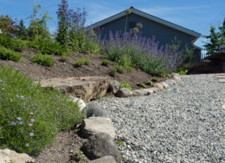 stor steinblokk lagt opp som benk i hage