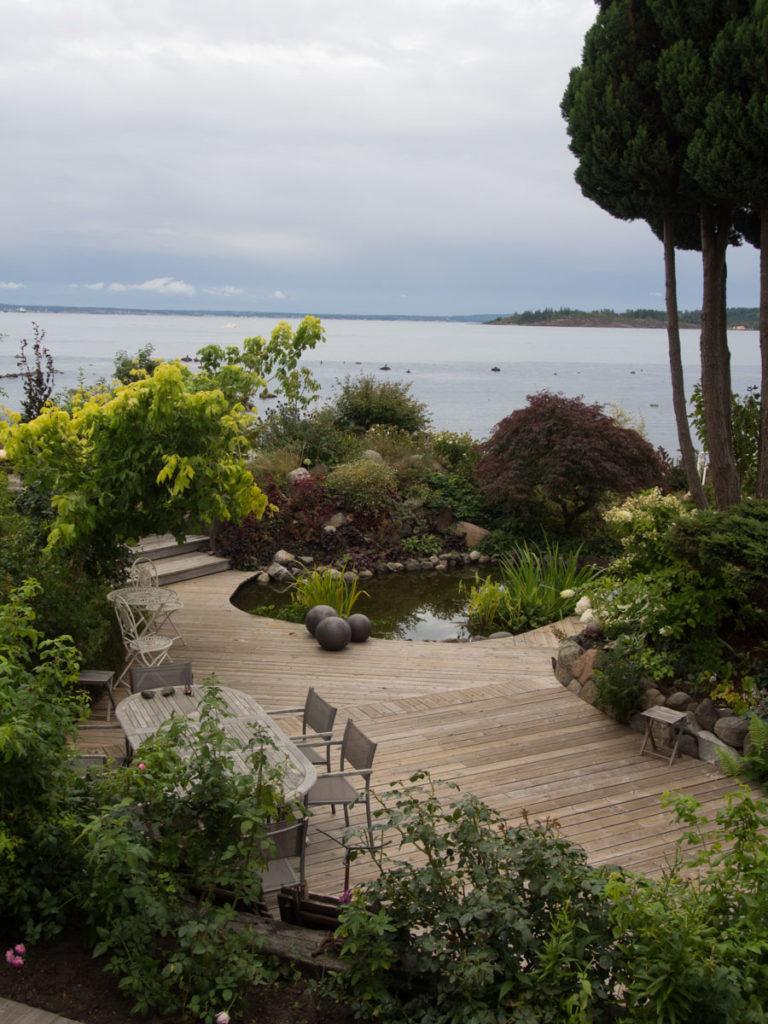 Hagedam i hage med terrasse og sitteplasser og bed