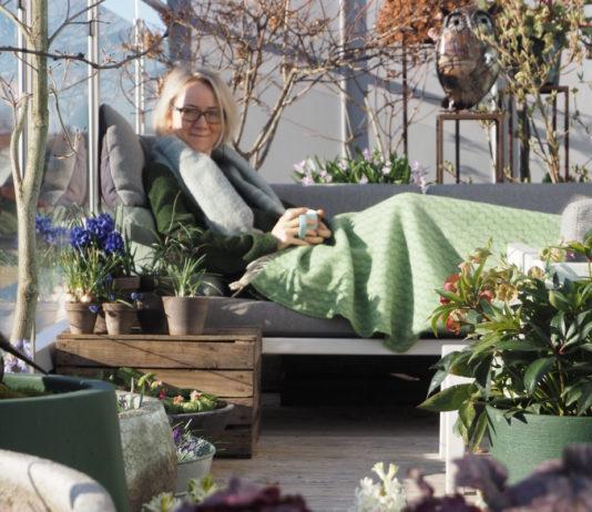 Anne sitter i utesofa med pledd, mellom krukker med planter